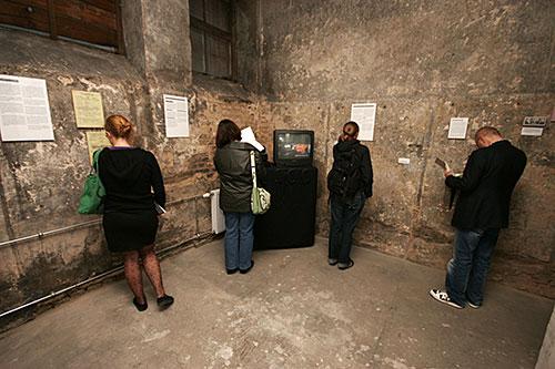 Gäste in der Dauerausstellung betrachten Exponate und das Zeitzeugeninterview mit Wolfgang und Via Breckheimer