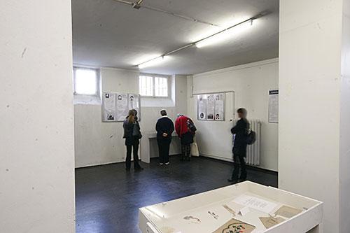 Im Vordergrund ist eine Vitrine mit Exponaten der Ausstellung »Frauen im Konzentrationslager« zu sehen. Im Hintergrund sehen sich Gästen Tafeln und Exponate an.